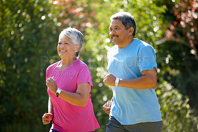 Buy stock photo Shot of a mature couple jogging together on a sunny day