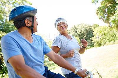 Buy stock photo Shot of a happy senior couple going for a bike ride and a jog together outdoors