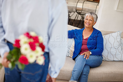 Buy stock photo Shot of a happy senior woman receiving a bunch of flowers from her husband