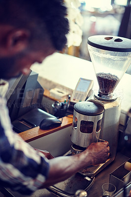 Buy stock photo Closeup shot of a male barista grinding coffee beans to make a fresh cup of coffee