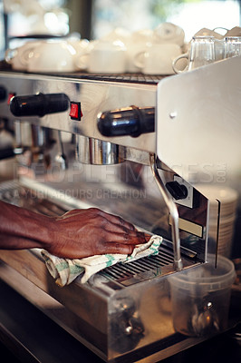 Buy stock photo Closeup shot of a barista cleaning an espresso machine at a cafe