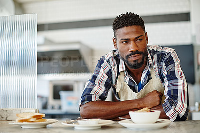 Buy stock photo Cropped shot of a handsome young man working in a coffee shop