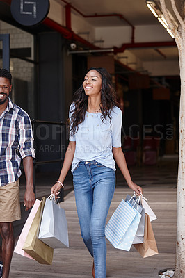 Buy stock photo Shot of a woman holding shopping bags while walking with her boyfriend