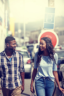 Buy stock photo Shot of a happy couple walking through an urban area