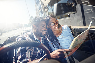 Buy stock photo Shot of a young couple reading a map while sitting in the car