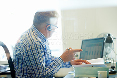 Buy stock photo A senior businessman wearing a headset discussing work while sitting at his computer