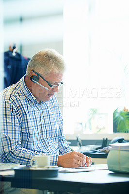 Buy stock photo A senior businessman wearing a headset writing down notes while on the phone at his desk
