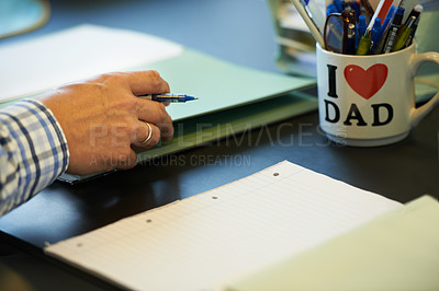 Buy stock photo Cropped image of a businessman sitting at his office desk with paperwork and stationary in front of him