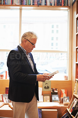 Buy stock photo Shot of a senior man browsing through a book at a bookshop