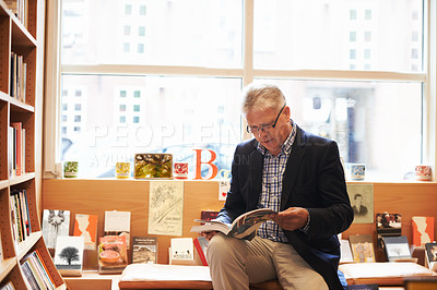 Buy stock photo Shot of a senior man sitting and browsing through a book at a bookshop
