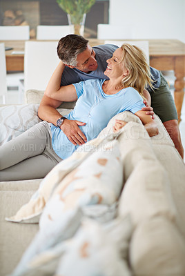 Buy stock photo Shot of a loving mature couple relaxing at home