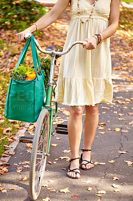 Buy stock photo Cropped shot of a young woman walking home from the grocery store with her bicycle