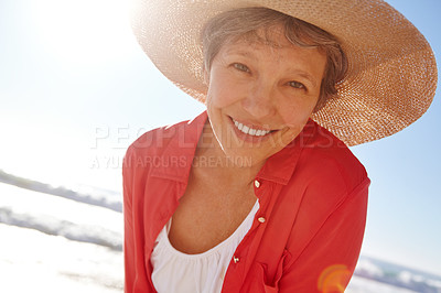 Buy stock photo Portrait of an attractive mature woman enjoying a day at the beach