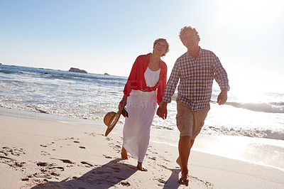 Buy stock photo Shot of a mature couple enjoying a late afternoon walk on the beach