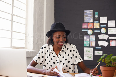 Buy stock photo Shot of a young designer making an entry in her diary