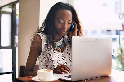 Buy stock photo Shot of an attractive young woman talking on a mobile phone while using a laptop in a cafe