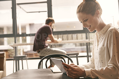 Buy stock photo Shot of a beautiful woman writing on her digital tablet in a coffee shop