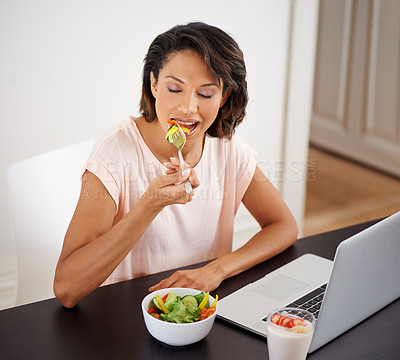 Buy stock photo Shot of a young woman enjoying a salad and working on a laptop at home