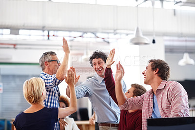Buy stock photo A group of designers high-fiving each other during an informal office meeting