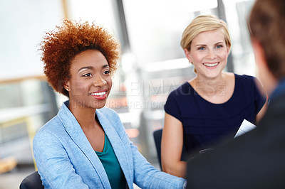 Buy stock photo Cropped shot of a young female designer in an informal meeting with her colleagues