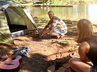 Buy stock photo Shot of a young couple on a camping trip together