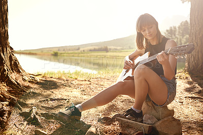Buy stock photo A young woman playing guitar while camping