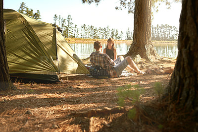 Buy stock photo Shot of a young couple camping by a lake