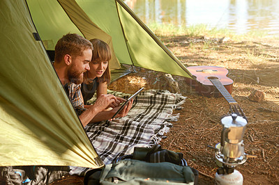 Buy stock photo Shot of a young couple lying in a tent looking using a digital tablet