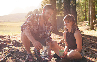 Buy stock photo Shot of a young couple making coffee on a camp stove while camping