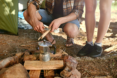 Buy stock photo Shot of campers preparing a campfire to make coffee