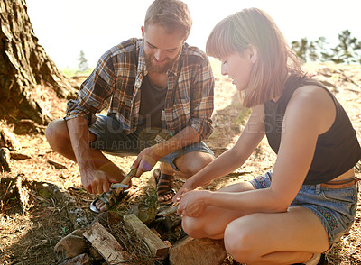 Buy stock photo Shot of a couple cutting kindling for a fire while camping