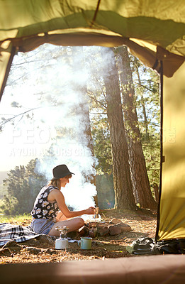Buy stock photo Shot of a young woman making coffee over an open fire at a campsite