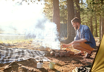 Buy stock photo Shot of a young man tending to a fire at his campsite