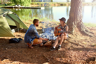 Buy stock photo Shot of a young woman playing guitar for her boyfriend at their campsit