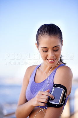 Buy stock photo Shot of a sporty young woman starting her music playlist before her workout