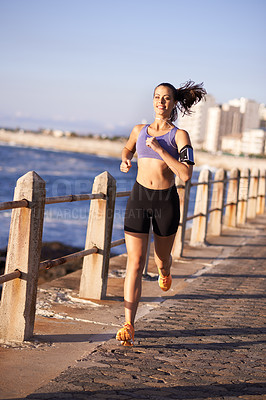 Buy stock photo Shot of an attractive woman jogging on the promenade