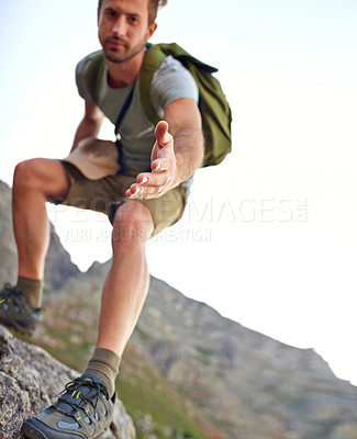 Buy stock photo Shot of a handsome young man offering you a hand up the mountain