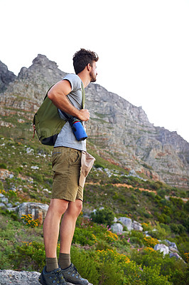 Buy stock photo Shot of a handsome young man enjoying the view while hiking