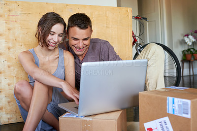 Buy stock photo Shot of an affectionate young couple using a laptop on the floor at home