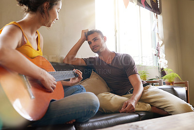 Buy stock photo Shot of a young woman playing the guitar while relaxing on the sofa with her husband