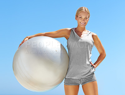 Buy stock photo Portrait of fit young woman holding an exercise ball against a blue sky