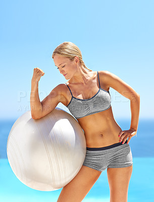 Buy stock photo Shot of an attractive young woman flexing her bicep on an exercise ball