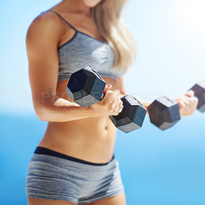 Buy stock photo Cropped shot of a fit young woman lifting weights outside