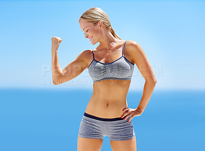 Buy stock photo Shot of an attractive young woman in exercise clothing flexing her bicep outside