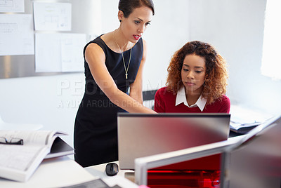Buy stock photo Shot of two attractive designers at work on a computer in the office