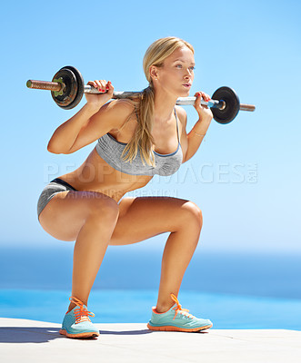 Buy stock photo Full length shot of an attractive young woman doing squats with a barbell outside