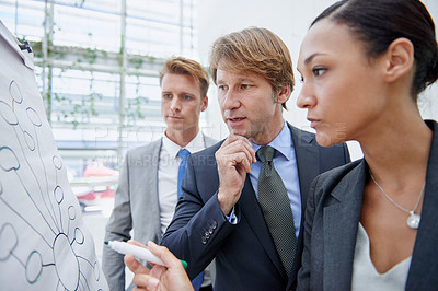 Buy stock photo A businesswoman drawing a diagram on a flip-chart as her colleagues stand by