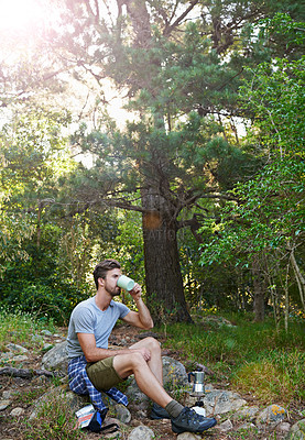 Buy stock photo Shot of a young man drinking a coffee while out on a hike