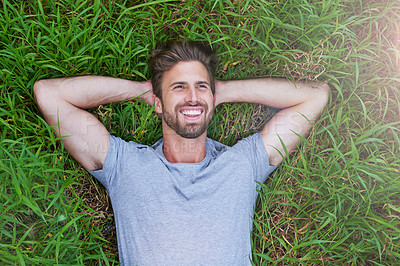 Buy stock photo High angle shot of a young man lying down on the grass with his hands behind his head