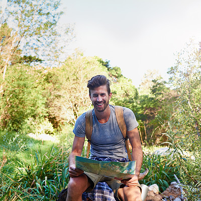 Buy stock photo Shot of a handsome hiker using a map